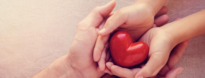 Hands holding a red cartoon heart