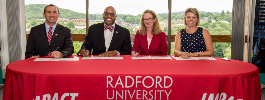 Represenatives from Radford University sign documents with NCI employees
