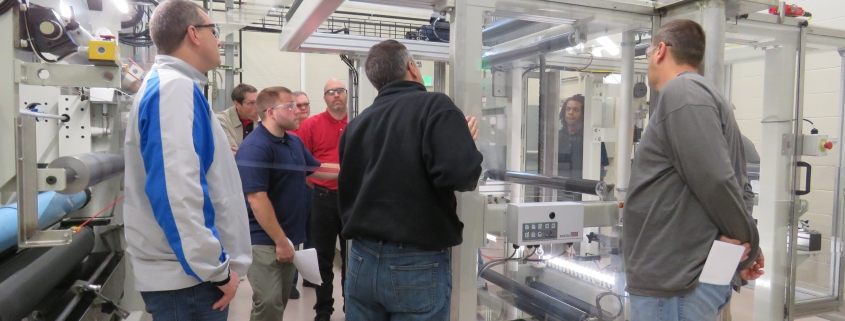 Visitors to NCI observe the Center of Advanced Manufacturing equipment