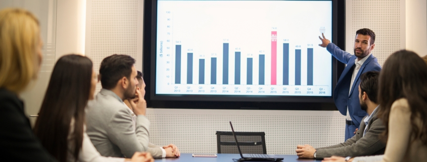Image of employees studying a graph in a meeting